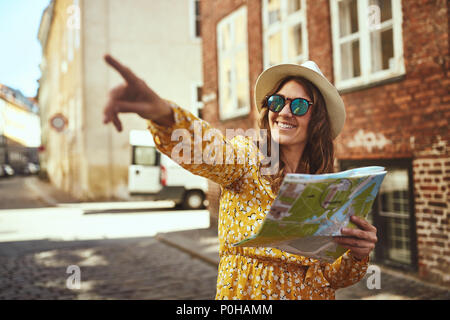 Smiling young brunette woman reading a map and pointing at sights while exploring the cobblestone streets of a city - Stock Photo