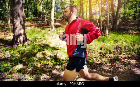 Fit young man in a jacket and shorts listening to music on earphones during a lone run along a forest path - Stock Photo