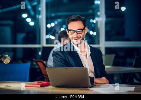 Handsome businessman with laptop working latenight. - Stock Photo