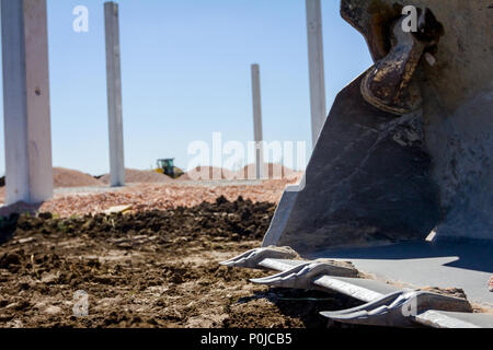 Excavator's tool, bucket, blade, tall concrete pillars are behind at building site. - Stock Photo