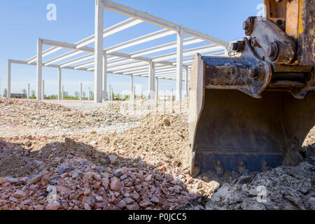 Excavator's tool, bucket, blade, tall concrete edifice is behind at building site. - Stock Photo