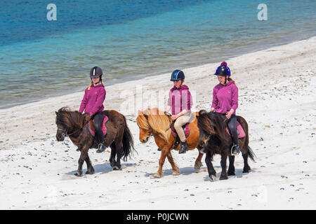 Three young girls / teenagers riding Shetland ponies on sandy beach along the Scottish coast on the Shetland Islands, Scotland, UK - Stock Photo