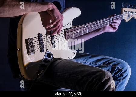 the man plays bass guitar on a black background, the music concept, beautiful lighting on the stage - Stock Photo
