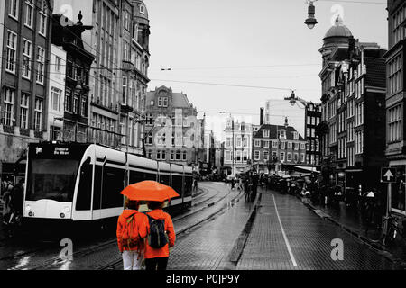 Unidentified people on the street of an old town of Amsterdam in the evening under the rain. - Stock Photo