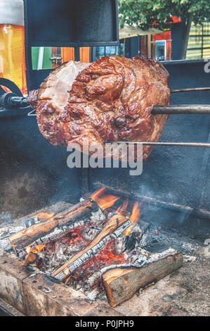 A spit for cooking roast shank in Prague on a Sunny day. National cuisine. The street food. The vertical frame. - Stock Photo