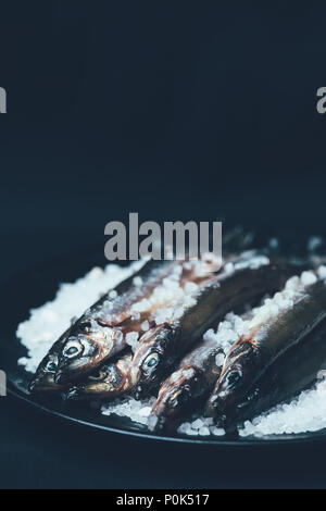 Pile of salted fish in frying pan isolated on black - Stock Photo