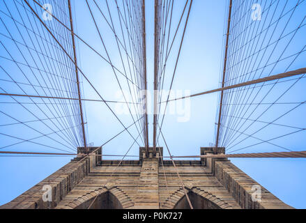 Looking up to one of the pillars of Brooklyn Bridge in New York City and at the pattern of the tensioned cable that support the bridge - Stock Photo