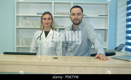 Friendly male and female nurses behind reception desk in hospital - Stock Photo
