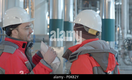 Two chemical factory workers having conversation in plant. - Stock Photo