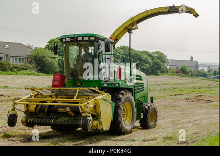 John Deere 7500 Combine Harvester at work collecting cut grass for silage on a farm in Schull, County Cork, Ireland. - Stock Photo