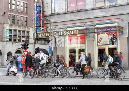 Bicycle riders stopping for red traffic light infront of Madame Tussaud's. Amsterdam is one of the most bicycle-friendly large cities in the world. - Stock Photo