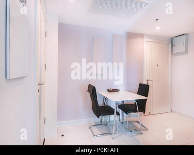 Modern white kitchen room interior decoration furniture with dining table set with a pair of black leather chairs with stainless steel frame - Stock Photo