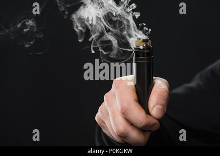 Cropped view of male hand activating electronic cigarette on black background - Stock Photo