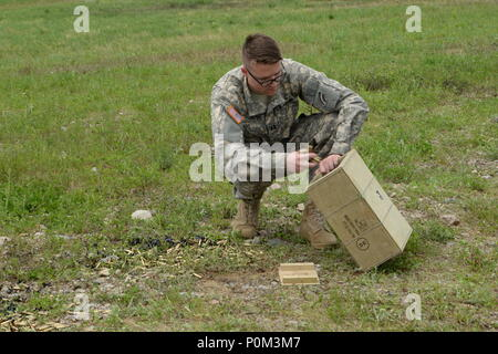 New York Army National Guard Capt. Forest Thrush, assigned to the 3rd Battalion, 142nd Aviation, collects brass shells on Fort Drum, N.Y., June 2nd, 2018. Soldiers had to qualify with M240s on the ground shooting at targets, before firing them from helicopters. (N.Y. Army National Guard photo by Spc. Andrew Valenza) - Stock Photo