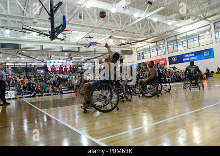 Army Spc. Vairon Caicedo Ocampo from Team SOCOM takes a shot against Navy in the wheelchair basketball game during the 2018 Warrior Games held at the Air Force Academy in Colorado Springs June 4, 2018.  Created in 2010, the DoD Warrior Games introduce wounded, ill and injured service members and veterans to Paralympic-style sports. Warrior Games showcases the resilient spirit of today's wounded, ill or injured service members from all branches of the military. These athletes have overcome significant physical and behavioral injuries and prove that life can continue after becoming wounded, ill  - Stock Photo