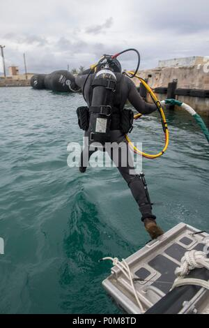 Construction Mechanic 2nd Class Andersen Gardner, from Fairport New York, attached to Underwater Construction Team (UCT) 2 performs dive operations in Apra Harbor, Guam June 6, 2018. UCT 2 specializes in the construction, inspection, maintenance, and repair of underwater and waterfront facilities in support of the Pacific Fleet. (U.S. Navy photo by Mass Communication Specialist 3rd Class Kryzentia Richards/Released) - Stock Photo