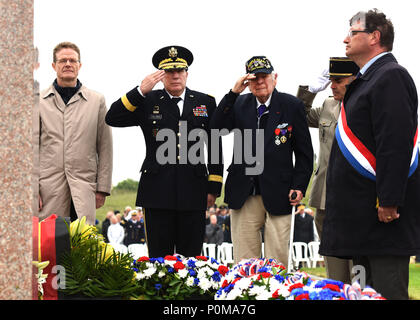 SAINTE-MARIE-DU-MONT, France (June 6, 2018) D-Day veteran John Roman (center) and Maj. Gen. Mark W. Palzer, commander of the 79th Theater Sustainment Command (center left), salute for the playing of French and U.S. taps during the Utah Beach Federal Monument Ceremony. This year marks the 74th anniversary of Operation Overlord, the Allied invasion of Normandy on June 6, 1944 -- most commonly known as D-Day. An epic multinational amphibious and airborne operation, D-Day forged partnerships and reinforced transatlantic bonds that remain strong today. Overall, U.S. service members from 20 units in - Stock Photo