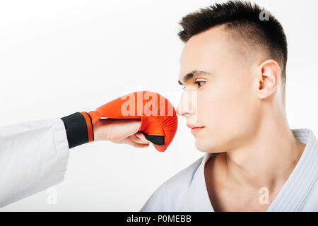 cropped image of karate fighter looking at hand in glove in front of face isolated on white - Stock Photo