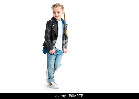 Little stylish kid wearing black leather jacket standing with fingers in pockets isolated on white - Stock Photo