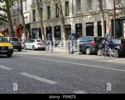 Three security officer from the city of Paris, wearing protective gear, ride bicycles down a Paris street, Paris, France - Stock Photo
