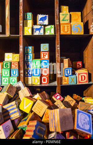 Shelf and Pile of colorful children's alphabet wooden block toys - Stock Photo