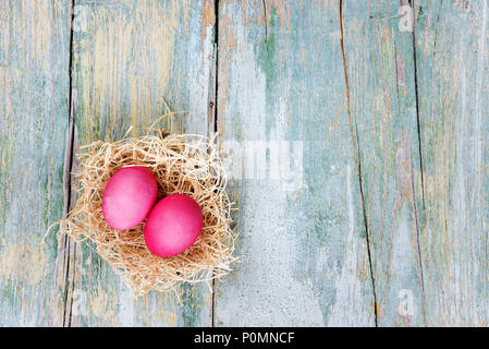 Easter composition with two red eggs in nest on the old blue wooden background, with copy-space, top view