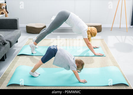 Mother and little boy practicing downward facing dog position on yoga mats - Stock Photo