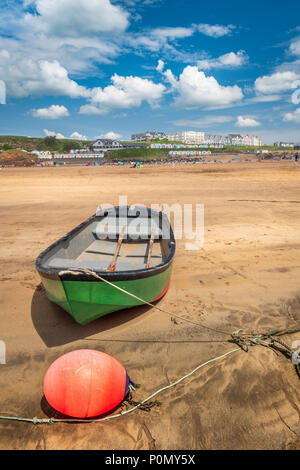 A solitary green boat is attached to it's moorings at low tide on the beautiful and popular sandy beach at Bude in North Cornwall. - Stock Photo