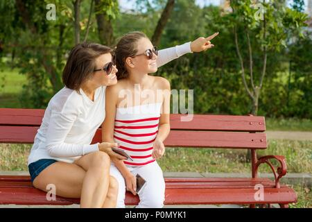 Communication between parent and child. Mom and daughter teenager talking and laughing while sitting on the bench in the park, Mother points with her  - Stock Photo