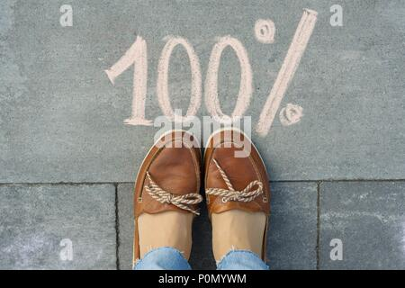 Female feet with text 100 percent written on grey sidewalk. - Stock Photo