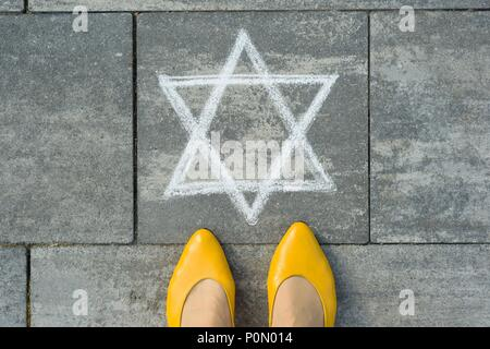 Female feet with abstract image of a six-pointed star, written on grey sidewalk - Stock Photo