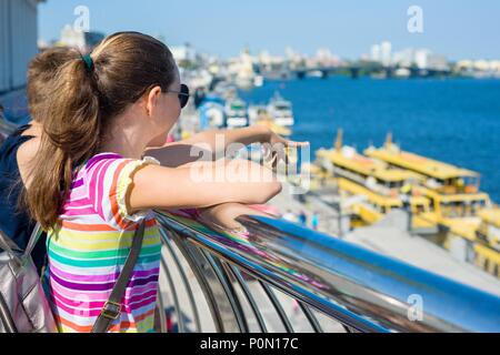Teenage student girl standing on the embankment near the river. - Stock Photo