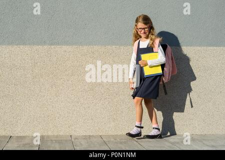 Schoolgirl with notebooks in hand. A girl with a backpack goes to school. Back to school! - Stock Photo