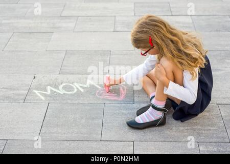 Picture gift for mother. A little girl draws colored crayons on the asphalt. Love mom. Mothers day - Stock Photo