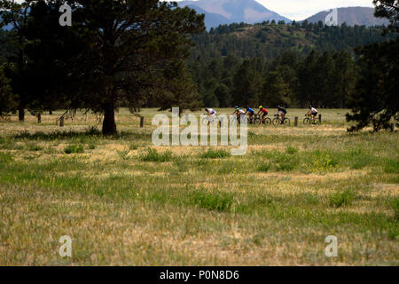 A peloton in the cycling distance race is seen off in the distance during the 2018 Warrior Games held at the Air Force Academy in Colorado Springs June 6, 2018. Created in 2010, the DoD Warrior Games introduce wounded, ill and injured service members and veterans to Paralympic-style sports. Warrior Games showcases the resilient spirit of today's wounded, ill or injured service members from all branches of the military. These athletes have overcome significant physical and behavioral injuries and prove that life can continue after becoming wounded, ill or injured.  (Photo by Michael Bottoms, US - Stock Photo