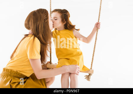 Daughter sitting on swing and kissing mother isolated on white - Stock Photo
