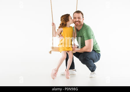 Little kid sitting on swing and kissing father isolated on white - Stock Photo