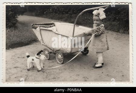 THE CZECHOSLOVAK REPUBLIC, CIRCA 1942: Vintage photo shows a small girl with dog toy and pram (baby carriage), circa 1942. - Stock Photo
