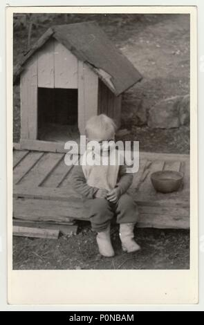 THE CZECHOSLOVAK REPUBLIC, CIRCA 1942: Vintage photo shows a small boy and kannel (doghouse), circa 1942. - Stock Photo