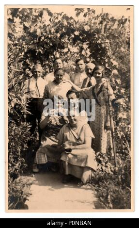 THE CZECHOSLOVAK REPUBLIC, CIRCA 1930: Vintage photo shows women and men in the back yard with grapes, circa 1930. - Stock Photo
