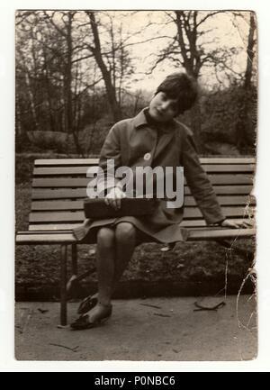 THE CZECHOSLOVAK SOCIALIST REPUBLIC, CIRCA 1960s: Vintage photo shows a young woman sit on a bench, circa 1960s. - Stock Photo