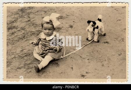 THE CZECHOSLOVAK REPUBLIC, CIRCA 1942: Vintage photo shows a small girl with dog toy, circa 1942. - Stock Photo