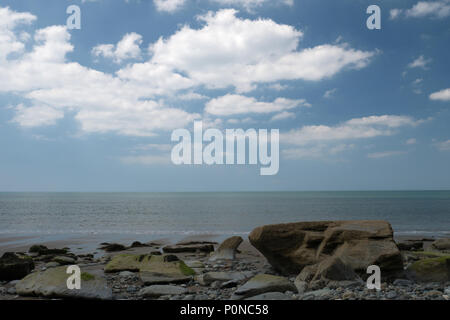 A flat calm sea in summer with white clouds on a blue sky. - Stock Photo