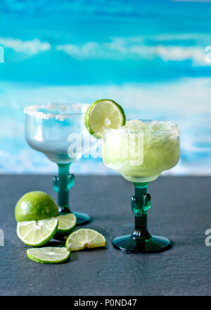 cold and icy frozen margarita drinks with slices of lime - Stock Photo