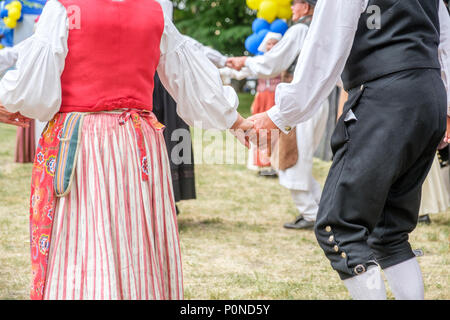Unrecognizable people dance Swedish folk dance during National day celebration in the Olai Park of Norrkoping. - Stock Photo