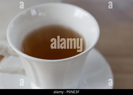 Hot black tea in white cup set on wooden table, morning time. - Stock Photo
