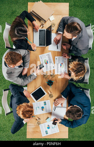 overhead view of business partners having discussion at table with documents and devices in office - Stock Photo