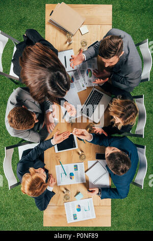 overhead view of angry business partners having discussion at table with documents and devices in office - Stock Photo