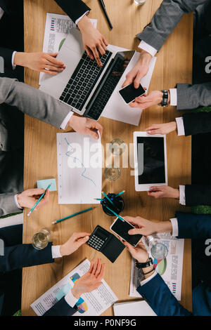 Cropped view of business colleagues showing digital devices to each other at table in ofifce - Stock Photo