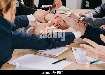 Cropped image of two business partners shaking hands while businesswoman holding their hands at table in office - Stock Photo